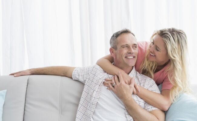 Content woman hugging his husband on the couch 000049105450_Large_650x400